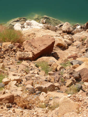 mineralized: Stones against Dead Sea, emerald water surface with water sediments Stock Photo