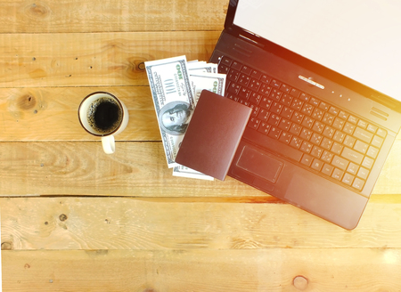 A labtop, passports, banknotes on the desk, prepare to travel to business. Stock Photo