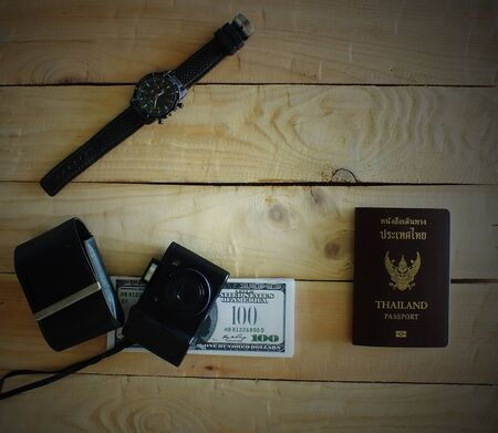 Travelers prepare before traveling abroad. Prepare passports, banknotes, wrist watches and compact cameras.Dark edges.
