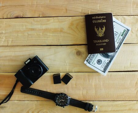 Travelers prepare before traveling abroad. Prepare passports, banknotes, wrist watches and the compact cameras.