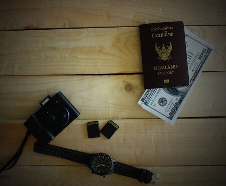 Travelers prepare before traveling abroad. Prepare passports, banknotes, wrist watches and the compact cameras.Dark edges.