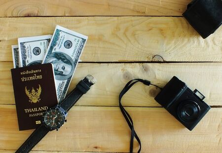 Travelers prepare before traveling abroad. Prepare passports, banknotes, wrist watches, compact cameras.