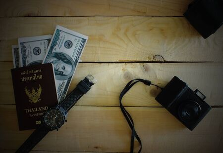 Travelers prepare before traveling abroad. Prepare passports, banknotes, wrist watches, compact cameras.Dark edges.