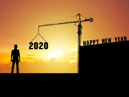 Happy new year 2020 An engineering man standing and watching the crane work Which is installing the letters Happy New Year 2020 at the top of the buildin 写真素材