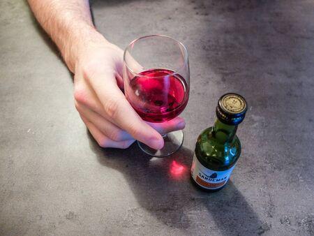 Charleroi, Belgium - December 28 2019: Close up of a man hand holding a glass of Sandeman porto
