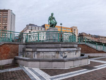 """Charleroi, Belgium - December 28 2019: Statue """"le Mineur accroupi"""" du Pont Roi Baudoin / Statue the Crounching miner at the King Baudoin Bridge - from Constantin Meunier"""