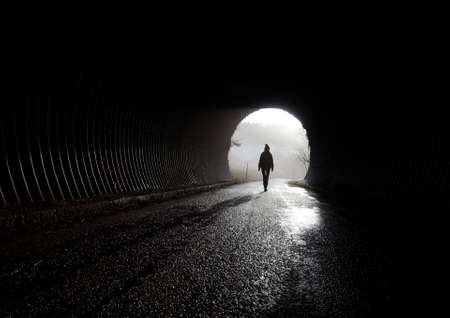 light at the end of tunnel, silhouette walking through the darkness Stock Photo