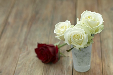 White roses in a lace detail vase with a red rose in the background on a wooden background Stock Photo - 10819191