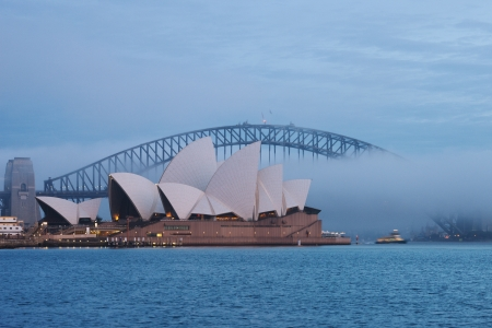 A foggy morning in Sydney Harbour creates artfully obscures the view of Harbour Bridge