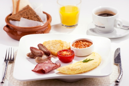 baked beans: A traditional breakfast consists of bacon, sausage, tomato, hash browns, egg   baked beans, accompanied by orange juice, coffee and toast Stock Photo
