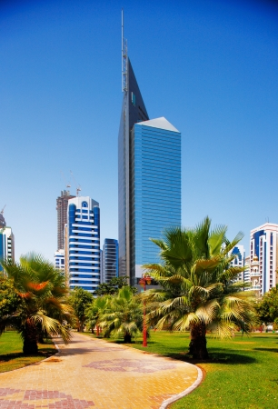 carlos: The architectural backdrop of city skyscrapers in Abu Dhabi contrasting with the beautiful landscape of the city park Editorial