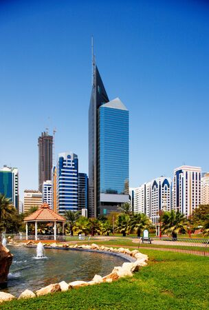 abu dhabi: The architectural backdrop of city skyscrapers in Abu Dhabi contrasting with the beautiful landscape of the corniche