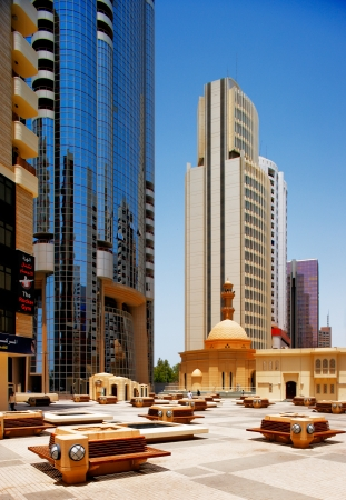 The contrast in architecture of Abu Dhabi, shows a contemporary skyscraper towering over a traditional mosque