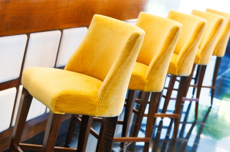 The warm yellow bar stools assemble in a beautiful diagonal row against the bar