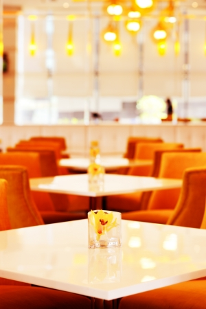 A contemporary restaurant awaits it s first customer  The setting of white tables is contrasted with the warm orange chairs photo