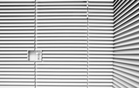 window shade: Locked up, louvered steel forms industrial art, punctuated by an embedded lock