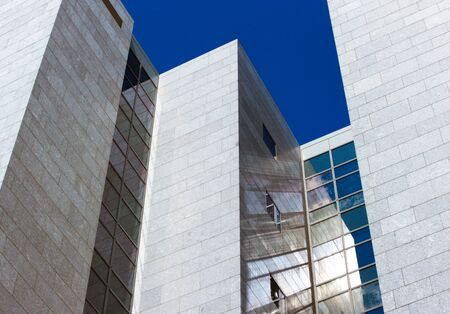Converging lines of contemporary architecture are punctuated by the suns rays to form wonderful reflections from the glass onto the granite wall