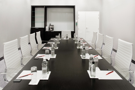 A boardroom is an essential corporate space for conducting meetings  This image shows a contemporary black   white boardroom Editorial