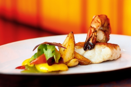 Seafood combo, consisting of cod   king prawn served with roasted wedges and capsicum photo