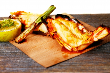 Grilled King Prawn Tikka with roasted asparagus and garnished with fresh lemon is an exotic rustic Indian recipe photo