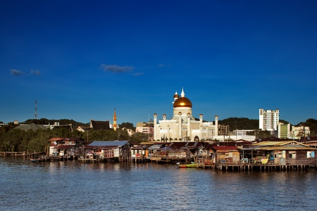 Brunei s capital Bandar Seri Begawan famed water village  In this image the Sultan Omar Ali Saifuddien Mosque forms a majestic backdrop Stock Photo
