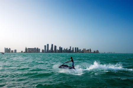 jet skier: A a jet skier cools down in turquoise waters of West Bay Doha, in view of flanked by the city skyline Stock Photo