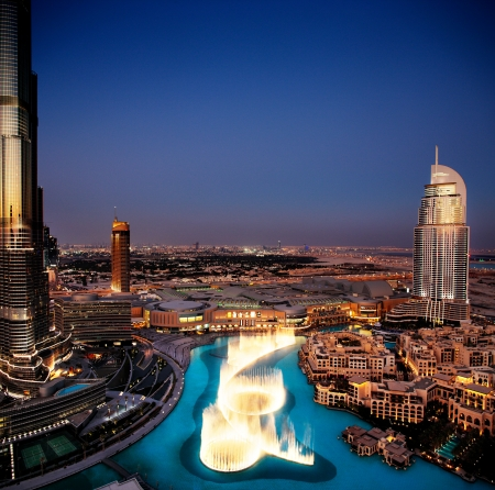 An overview of the spectacular Dubai Dancing Fountain as it dances to the music at dusk  It is overlooked by Burj Khalifa, Dubai Mall and The Address Hotels