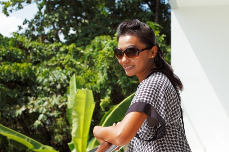 Young woman in sunglasses standing on a balcony and smiling photo