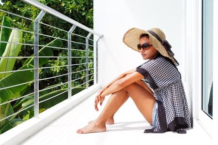 стиль жизни: Молодая женщина в шляпу и солнцезащитные очки сидения вниз на балконе и наслаждаясь видом Фото со стока