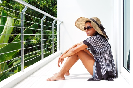 Young woman in a hat and sunglasses seating down on a balcony and enjoying the view Stock Photo