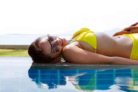 Young woman in a yellow swimsuit and sunglasses laying down on the edge of a swimming pool and having a sun bath on a sunny summer day Stock Photo