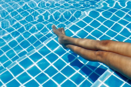 A legs of a young woman in a swimming pool on a sunny summer day Stock Photo