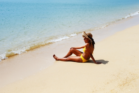 sun bathing: Young woman in a yellow swimsuit, a hat and sunglasses seating down on a sandy beach and sun bathing on a sunny summer day