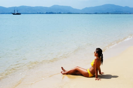 Young woman in a yellow swimsuit and sunglasses seating down on a sandy beach of Thailand and sun bathing on a sunny summer day photo