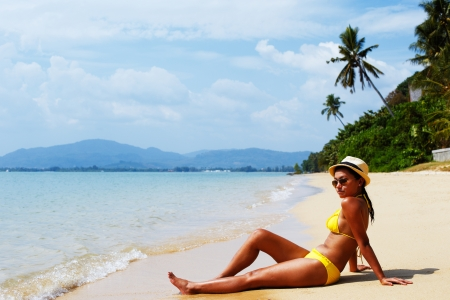 sun down: Young woman in a yellow swimsuit, a hat and sunglasses seating down on a sandy beach of Thailand and sun bathing on a sunny summer day