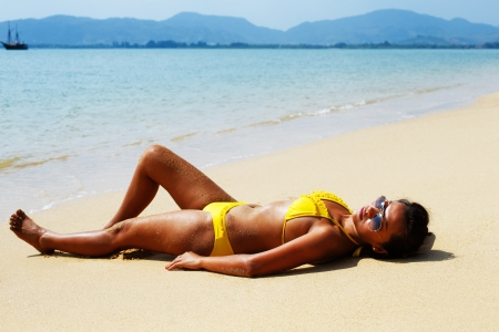 Young woman in a yellow swimsuit and sunglasses laying down on a sandy beach of Thailand on a sunny summer day