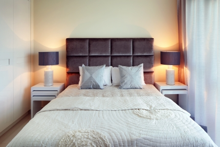 bedding indoors: The bed is perfectly made  The dark chocolate headboard contrasts beautifully against the cream backwall
