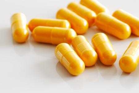 A handful of  turmeric capsules on white reflective ceramic surface against a white background