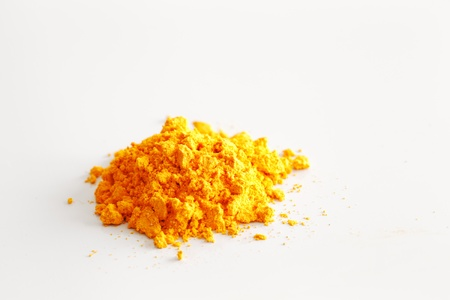 valerian: A macro image of the contents of a single turmeric capsule on white reflective ceramic surface Stock Photo