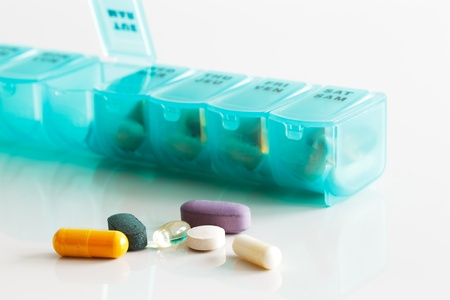 A weekly container of tablets, vitamins etc  on white reflective ceramic surface