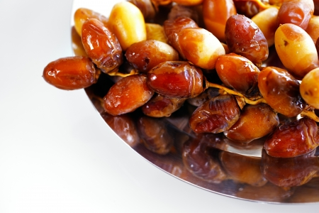 A tray of Arabic dates on a white background photo
