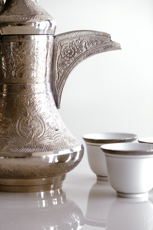 An abstract detail of a handle of a Dallah  A dallah is a metal pot with a long spout designed specifically for making Arabic coffee
