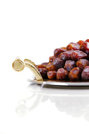 Dried Arabic dates presented on an ornate tray and shot against a white background Stock Photo