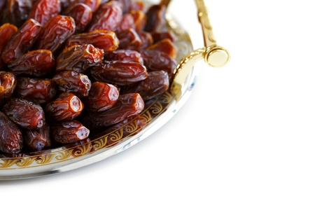 dates fruit: Dried Arabic dates presented on an ornate tray and shot against a white background Stock Photo