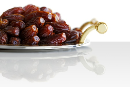 Dried Arabic dates presented on an ornate tray and shot against a white background photo