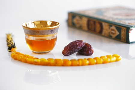 The Masbaha is also known as Tasbih photographed here with the Quran, Arabic Tea and dried dates - all symbols of Ramadan Stock Photo