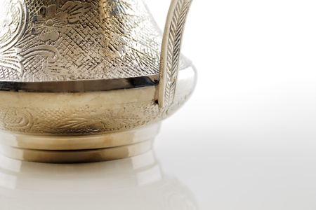 specifically: A close up crop of an ornate dallah which is a metal pot with a long spout designed specifically for making Arabic coffee Stock Photo
