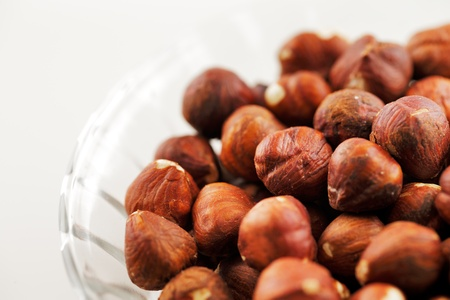 comestible: A bowl of hazelnuts shot against a white background