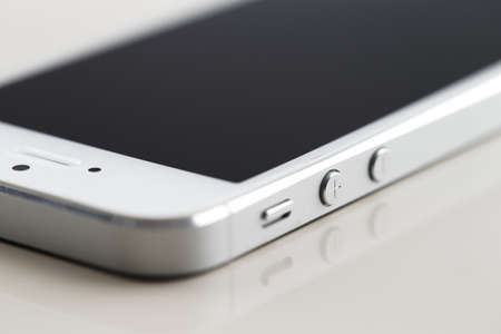 touch screen phone: A close-up of a new white smartphone on a white reflective background