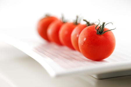 Fresh organic tomatoes with water droplets creatively photographed in an abstract manner on a white ceramic plate Stock Photo - 22169973